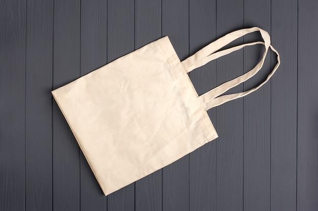 Экологичная нетканая сумка на темно-сером деревянном столе