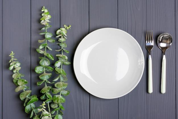 スプーン、フォーク、グレープレート、グレーの木製テーブルに緑のユーカリの小枝