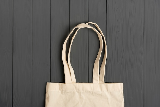 ダークグレーの木製テーブルにエコフレンドリーな不織布バッグ