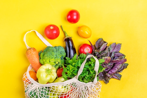 Эко дружественных сетки магазин сумка с органическими зелеными овощами на желтом. плоская планировка, вид сверху.