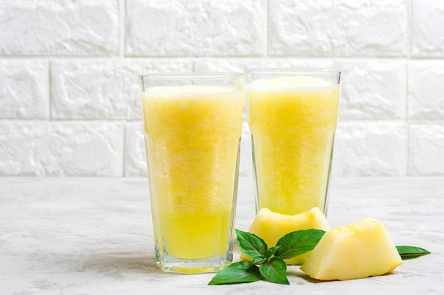 メロンレモネード、グレーのテーブルの上のグラスに氷とバジルのスムージー。夏の爽やかなデトックスドリンクラスティックスタイル