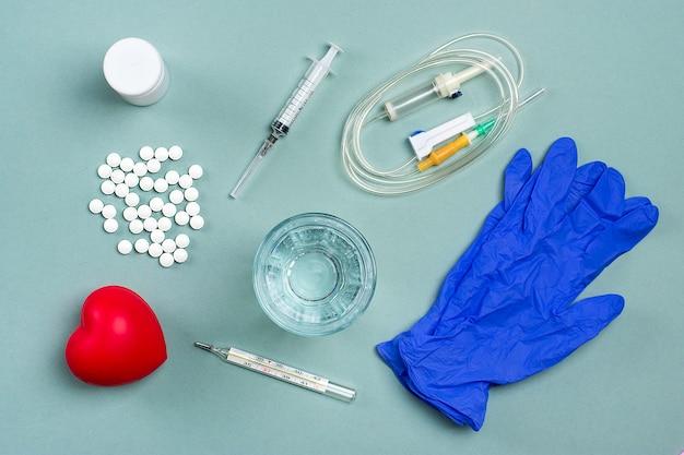 Лекарства, таблетки, стакан воды, термометр, лекарства для лечения простуды, гриппа, жара на сером фоне.