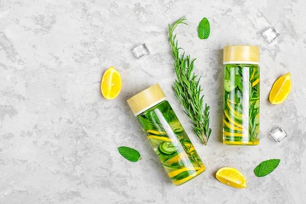 注入水、カクテル、レモネードまたはお茶。夏は、レモン、タラゴン、ライム、きゅうり、灰色のコンクリート背景にミントの葉と冷たい飲み物をアイス。平干し。上面図。