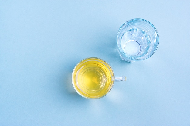 青いテーブルの上の水のグラス