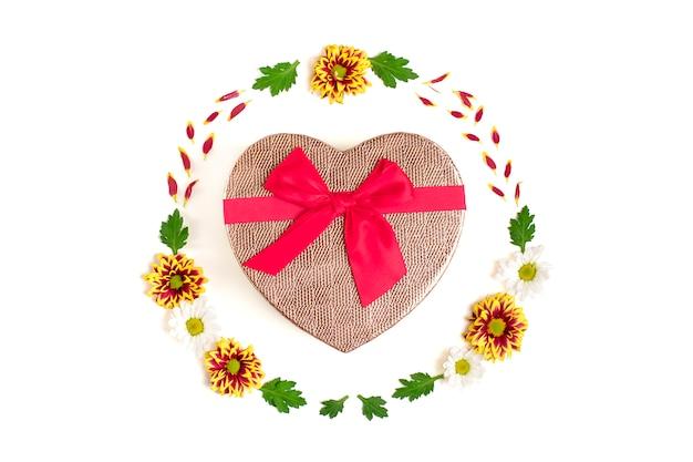 ハート、黄色、赤、白のアスターの花、白で隔離される緑の葉のギフトボックスの形