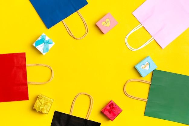 Разноцветные пакеты для упаковки, подарочные коробки на желтом фоне вид сверху плоская планировка