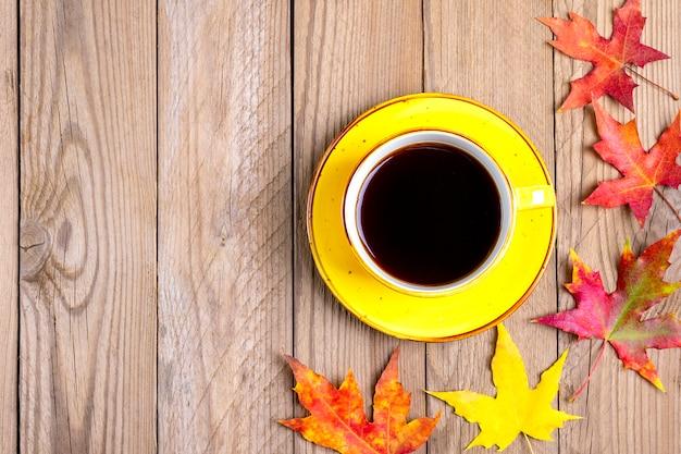 秋の落ちた黄色、オレンジ、赤の葉の木製テーブルの上のホットブラックコーヒーカップ