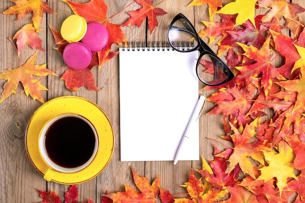 ブラックコーヒー、グラス、黄色のロリポップ、マカロン、メモ帳、秋の落ち葉と木製のテーブルとカップフラットレイアウト