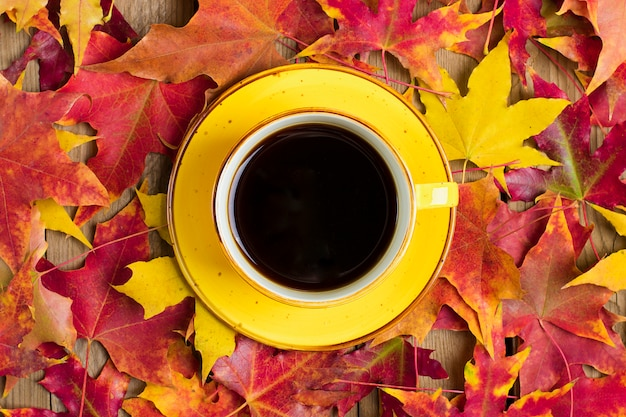 秋の落ちた黄色、オレンジ、赤の葉を持つ木製のテーブルにホットブラックコーヒーとカップフラットレイアウト