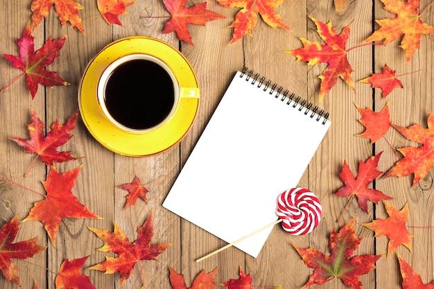 ブラックコーヒー、黄色のロリポップ、メモ帳、秋の落ちたオレンジの葉と木製のテーブルとカップフラットレイアウト