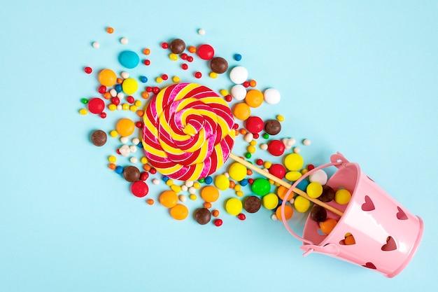 青いフラットに心でバケツからこぼれたカラフルなチョコレート菓子