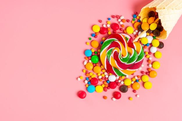 ピンクのフラットにアイスクリームワッフルコーンからこぼれたカラフルなチョコレート菓子をミックスします。