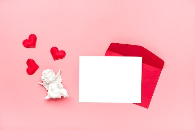 赤い封筒、白い筆記用紙、ピンクの背景にハートハッピーバレンタインデーのコンセプト