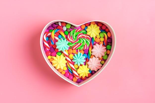 Микс шоколадных конфет лежат в подарочной коробке в форме сердца на цветном фоне
