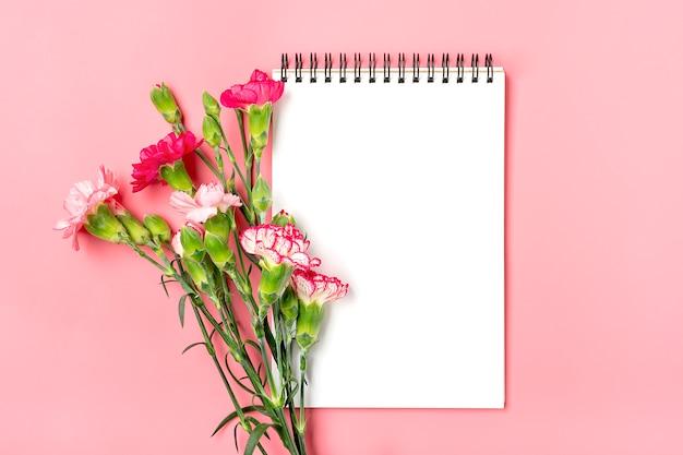 異なるピンクのカーネーションの花、ピンクの背景に白いノートのカラフルな花束