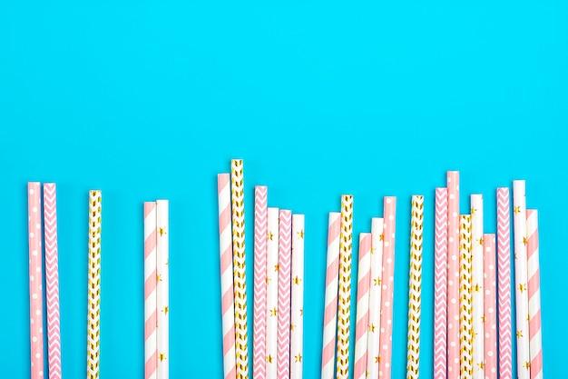青の背景に金色、白、パステルピンクのストライプとパーティーの紙ストローを飲む