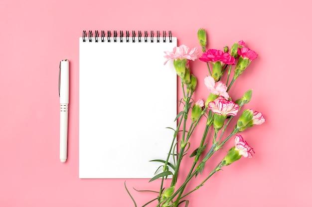 別のピンクのカーネーションの花、白いノート、ピンクの背景のペンのカラフルな花束