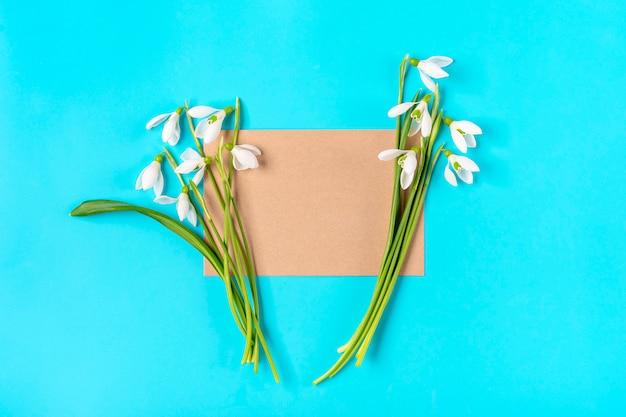 Букет цветов подснежников и крафт-бумаги для заметок на синем фоне. плоская планировка. вид сверху.