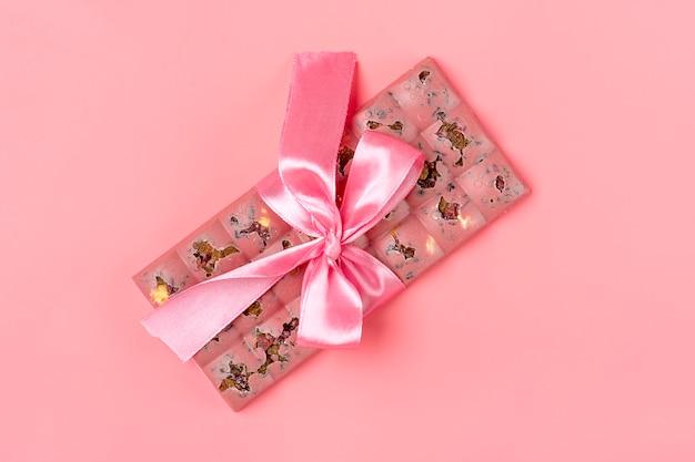 レーズンとピンク色の背景にデザートコンセプトに分離されたナッツとピンクのフルーツチョコレート