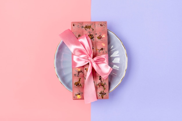 レーズンとナッツのライラック色の背景に分離されたピンクのフルーツチョコレートデザートタイムコンセプトキャンディショップ