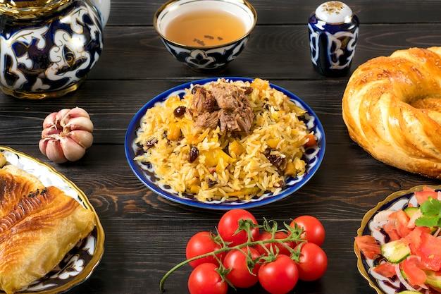 国立ウズベキスタンのピラフ、肉、トマトのアチチュクサラダ、キュウリ、タマネギと伝統的なプレート