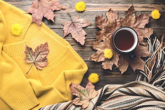 秋のファッション季節のコンセプトセーターカーディガンスカンジナビアのニットスカーフカップホット紅茶