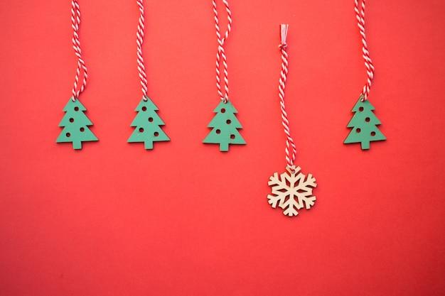 木製のクリスマスのおもちゃ、赤い背景に祭りのクリスマスの装飾