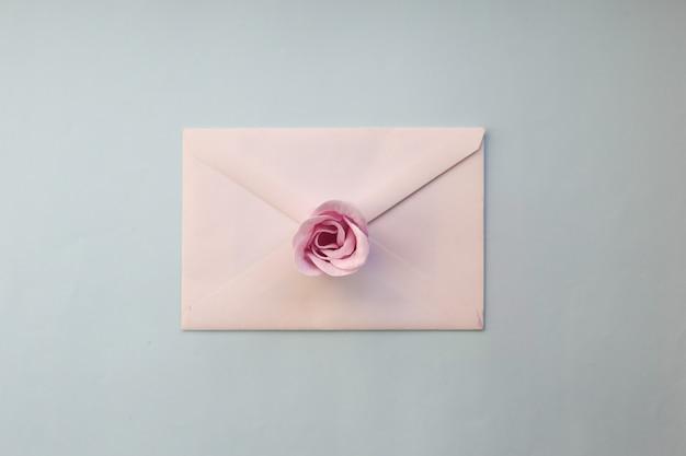 白い封筒、青い背景にピンクのバラの花。ミニマルフラットレイ