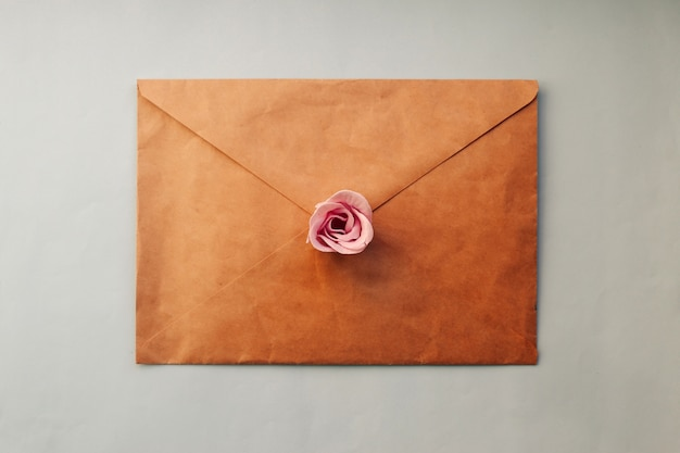 古い茶色の封筒、青い背景にピンクのバラの花。ミニマルフラットレイ