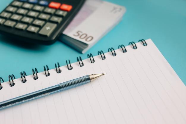 ユーロ紙幣と青い背景上の電卓のパック