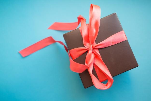 Коричневая подарочная коробка с красной лентой на синем фоне. вид сверху с копией.