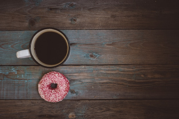 Свежий пончик с чашкой кофе на деревянный стол