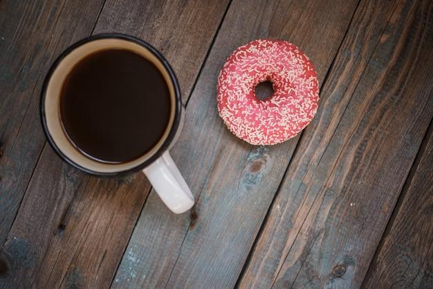木製のテーブルの上のコーヒーカップと新鮮なドーナツ