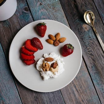 Тарелка с творогом, клубникой и орехами, чашкой кофе и полотенцами на деревянном столе, здоровое питание, завтрак