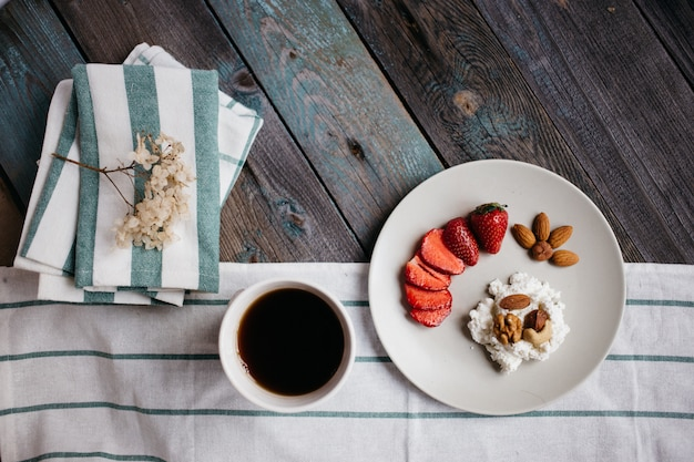 カッテージチーズ、イチゴとナッツ、一杯のコーヒーと木製のテーブルの上のタオル、健康食品、朝食プレート