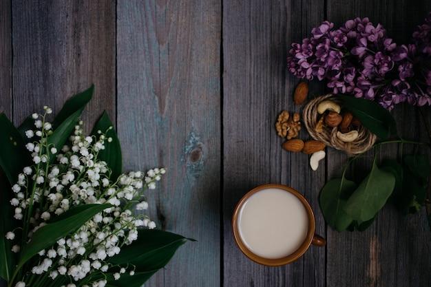 Чашка чая, орехи, букет из лилий на деревянном фоне