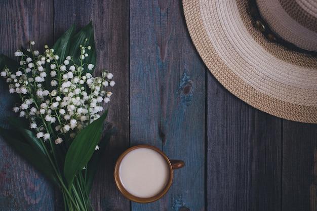 Букет ландышей, чашка кофе, чай, молоко, на деревянном фоне