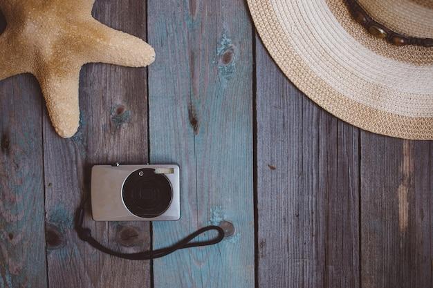 帽子、カメラ、ヒトデ、木製の背景に