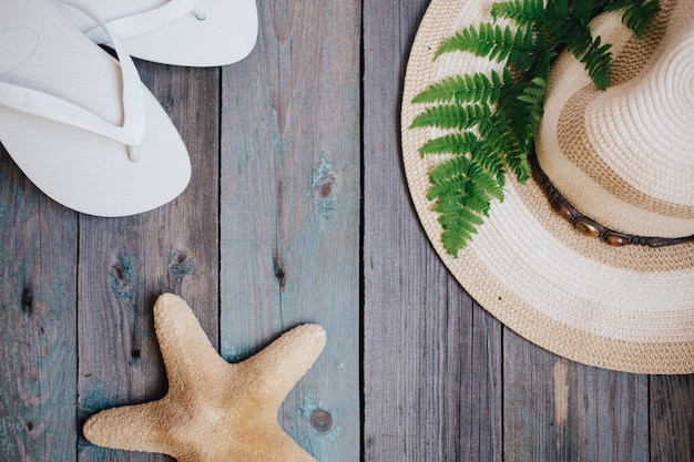 帽子、シダの葉、ヒトデ、木製の背景にフリップフロップ