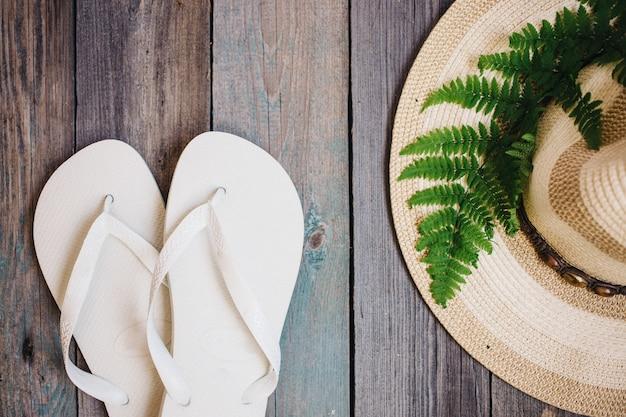 帽子と白いフリップフロップが木製の背景に浮かぶ