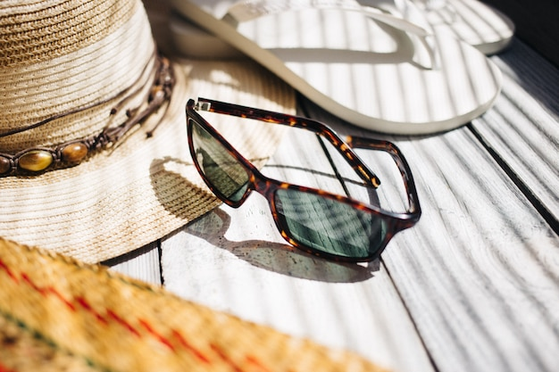 帽子、白いフリップフロップ、サングラス、白い木製の背景にビーチバッグ