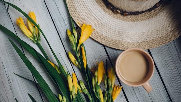 Букет из желтых лилий, шляпа и чашка кофе на деревянном столе, завтрак