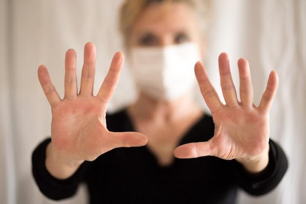 マスクを身に着けている年配の女性は、きれいな手を示し、ストップハンドを示しています。セレクティブフォーカス。