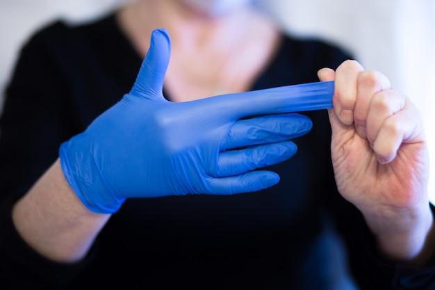 年配の女性がマスクを着用し、手から手袋を取り外します。セレクティブフォーカス。コロナウイルスと流行性ウイルスの症状。