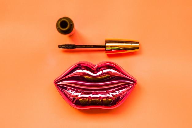 シャイニングピンクの唇、明るいオレンジの背景にマスカラ、メイクと美容のコンセプト
