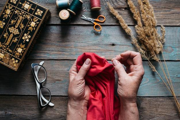 Женские руки шить на деревянный стол, ножницы, шкатулка, нитки, очки