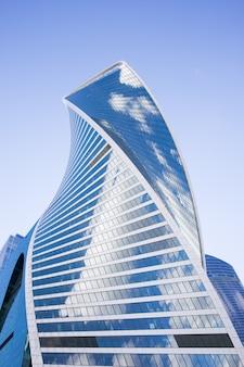 雲の反射を伴う未来的なデザインのモスクワ市の高層ビルの底面図