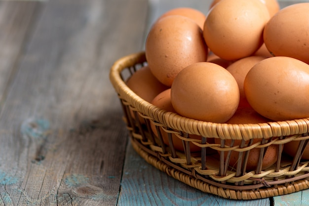 茶色の農家ケージフリー鶏卵、バスケット、クローズアップ、素朴なテーブル