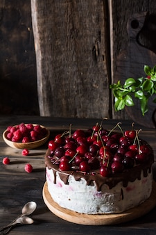 チョコケーキ。チェリーケーキ、チョコレート入り。木製のプレートのラズベリー。デザート。