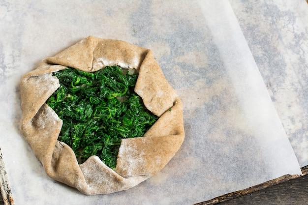 ほうれん草と夏のガレット。夏の食べ物、開いたパイ、焼きの過程、生の生地。